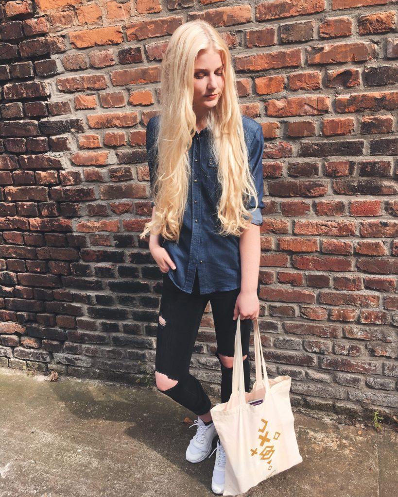 benita mit lockigen haaren und einem goodiebag vom duesseldorfer fashionyard
