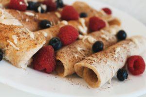 gesunde protein crêpes getoppt mit protein cream, heidelbeeren und himbeeren