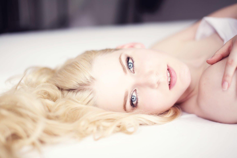 ein portrait von benita, liegend auf dem bett mit langen, lockigen haaren