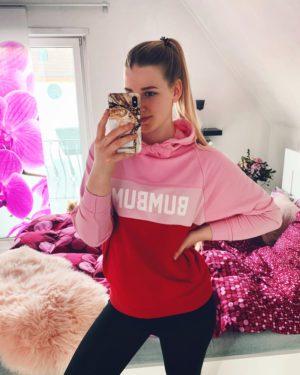 ein spiegelselfie von benita in ihrem schlafzimmer. sie traegt einen rosa-roten hoodie von bumbum