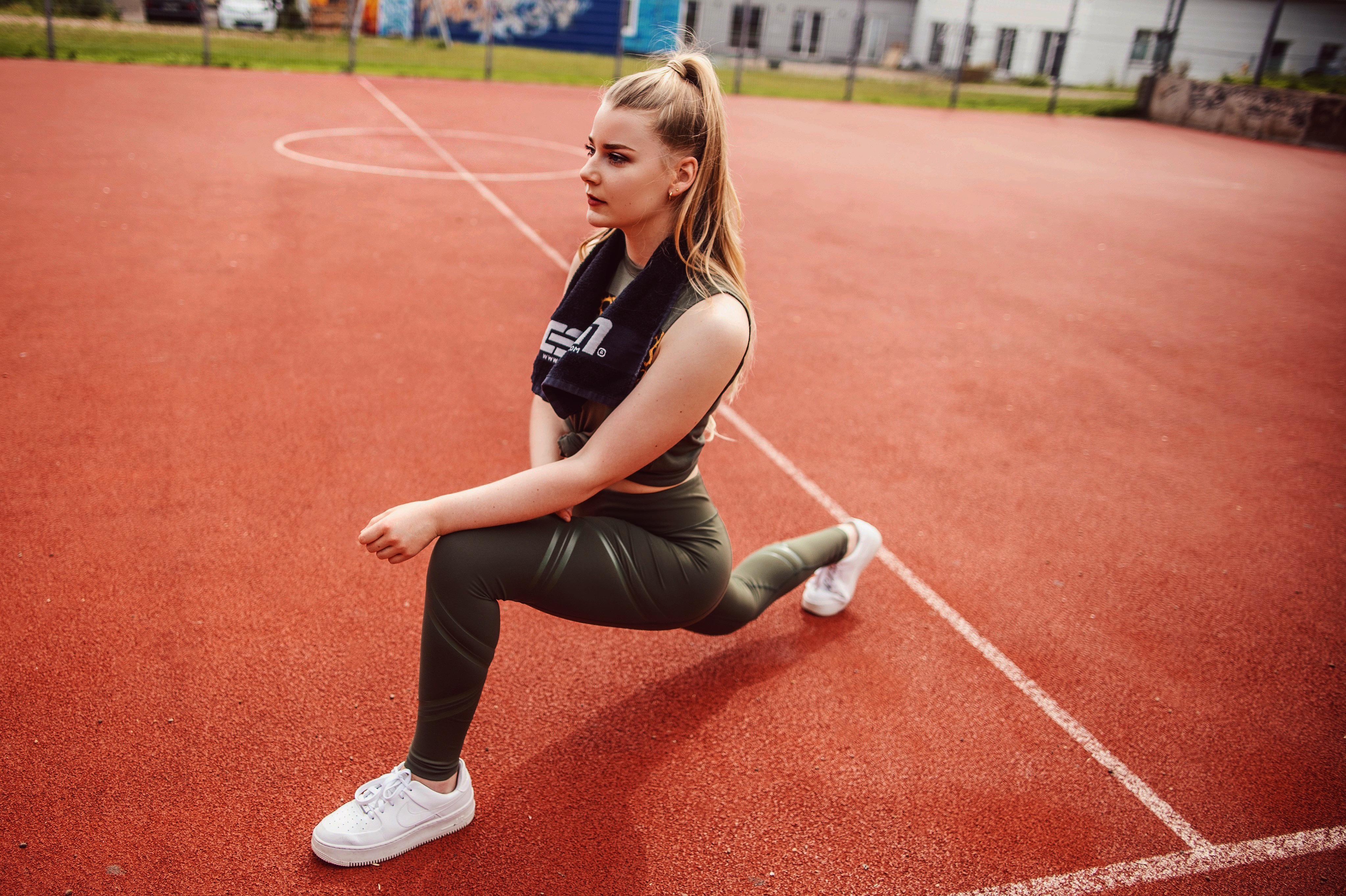 benita zeigt eine dehnpose für die beine auf einem sportplatz in bielefeld