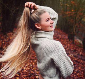 benita in dem wald der externsteine. zu sehen sind ihre langen haare in einem pferdeschwanz