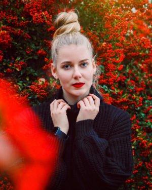 portrait von benita thenhaus vor einem strahlend roten busch