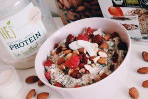 protein porridge mit gefrorenen beeren, kokosraspeln und mandeln
